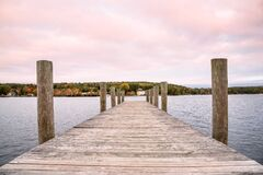 Empty pier on a lake under colourful sky at dusk