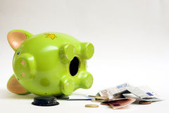 Empty piggy bank. An open green piggy bank on its side with money lying nearby.  White background Royalty Free Stock Photos