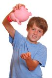 Empty piggy bank. Portrait of a desperate teenage boy trying to empty his piggy bank Royalty Free Stock Image