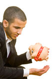 Empty piggy bank. Young business man holding his hand under an empty piggy bank Stock Photo