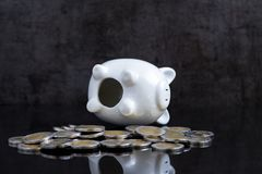Empty piggy bank lay on dark black table with coins using as bro royalty free stock images