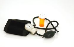 Empty pill bottle with blood pressure manometer Royalty Free Stock Images