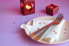 Empty pink plate, cutlery, hearts, candlesticks and red gift on pink-purple background. St. Valentine`s Day table setting concept royalty free stock images
