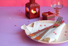 Empty pink plate, cutlery, hearts, candlesticks, wine glasses and red gift on pink-purple background. St. Valentine`s Day table royalty free stock image