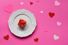 Empty pink plate, felt hearts and red gift on pink background. St. Valentine& x27;s Day concept. Top view, flat lay. Copy space.  stock images