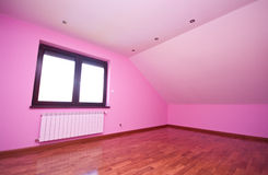 Empty pink room. Interior details of empty modern room decorated in pink with wooden laminate floor, window and radiator Stock Photography