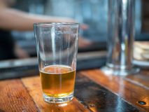Almost empty pint glass of beer sitting on bar for last call stock photo