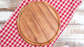 Empty pizza board on empty wooden table with tablecloth,napkin - top view royalty free stock photography