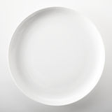Empty plain white generic dinner plate. Empty plain white round generic dinner plate with place for placement of food or a recipe viewed close up overhead over a Royalty Free Stock Images