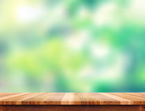 Empty plank brown wood table top with blur green tree background royalty free stock image