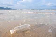 Empty plastic bottle on the beach in the morning. Stock Photo