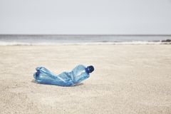 Empty plastic bottle on a beach. Selective focus, color toning applied stock photography