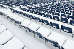 Empty plastic chairs covered in snow Royalty Free Stock Photo