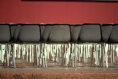 Empty plastic chairs and red wall Royalty Free Stock Photo