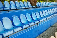 Empty plastic chairs in the stands of the stadium Stock Photo