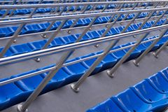 Empty plastic chairs in the stands of the stadium. Many empty seats for spectators in the stands. stock photo