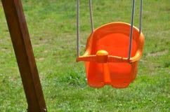 Empty plastic swing. Child orange empty plastic swing Stock Image