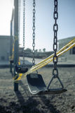 Empty plastic swings on playground with caution tape, selective focus Stock Image