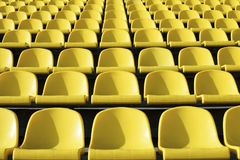 Empty plastic yellow seats at stadium, open door sports arena. stock photography