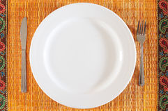 Empty plate. A round empty plate on a patterned bamboo mat, with a knife and fork Stock Images