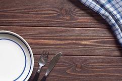 Plate and cutlery. Empty plate with blue stripes and cutlery on brown wooden table, top view. Space for text Royalty Free Stock Image
