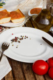 Empty plate and bread  with tomatoes and olive oil Stock Photography
