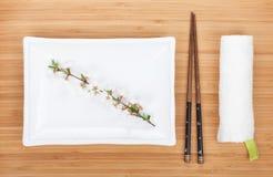 Empty plate, chopsticks and sakura branch Royalty Free Stock Image