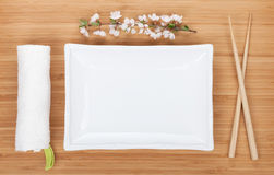 Empty plate, chopsticks and sakura branch Royalty Free Stock Images