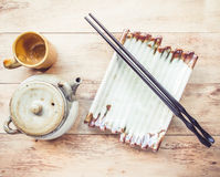 Empty plate and chopsticks, tea pot on wooden table Stock Photography