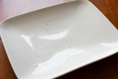 Empty plate. Close up look of white rectangular plate with some food stain and small bread crumb on brown wooden table Royalty Free Stock Images