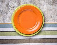 Empty plate on concrete table. Empty orange and green plates on concrete table stock image