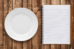 Empty plate and cookbook. On table Royalty Free Stock Photo