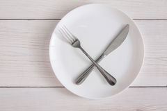 Empty plate with crossed fork and knife on white wood top view. Empty plate with crossed fork and knife. Dish and cutlery top view on white wood table background royalty free stock photos