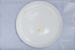 Empty plate with crumbs leftovers from Pizza. Empty white plate with crumbs and sauce left from a Pizza Salami. On blue checkered table cloth, part of an image Royalty Free Stock Image
