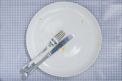 Empty plate with crumbs leftovers from Pizza. Empty white plate and silverware with crumbs and sauce left from a Pizza Salami. On blue checkered table cloth Stock Photo