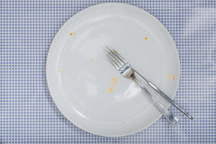 Empty plate with crumbs leftovers from Pizza. Empty white plate and silverware with crumbs and sauce left from a Pizza Salami. On blue checkered table cloth Stock Images