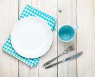 Empty plate, cup and silverware. Over white wooden table background. View from above Royalty Free Stock Photo