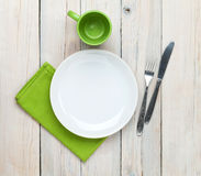 Empty plate, cup and silverware. Over white wooden table background. View from above Stock Photos