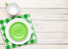 Empty plate, cup and towel over wooden table background. View from above with copy space Royalty Free Stock Image