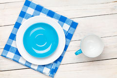 Empty plate, cup and towel over wooden table background Royalty Free Stock Photography
