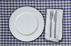 Empty plate and cutlery on blue-white checkered cloth.  Royalty Free Stock Image