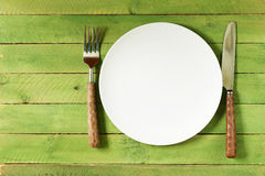 Empty plate with cutlery and napkin. On wooden background Stock Image