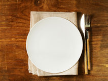 Empty plate with cutlery and napkin Royalty Free Stock Image