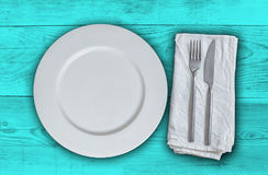 Empty plate with cutlery on petrol wood background Stock Photos