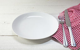 Empty plate with cutlery and red white napkin on a white rustic Royalty Free Stock Photo
