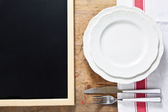 Empty plate with cutlery on a wooden background and a black chal Royalty Free Stock Photo