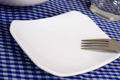 Empty plate on a dining table Royalty Free Stock Images