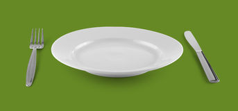 Empty plate or dish for food with fork and knife. On green table Stock Image