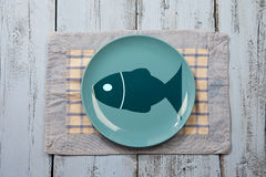 Empty plate with fish illustration. On light blue wooden background Royalty Free Stock Photos