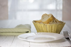 Empty plate, fork and a basket of bread Royalty Free Stock Photography
